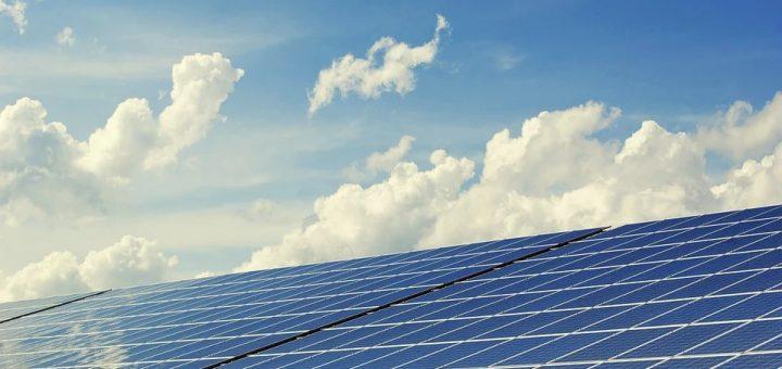Große Solarthermieanlage, im Hintergrund blauer Himmel mit Wolken und Sonenstrahlen