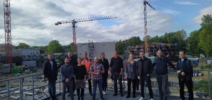 Das Foto zeigt eine 12-köpfige Gruppe Menschen (Besuch aus Kladno und Prag)vor der Kulisse einer Baustelle